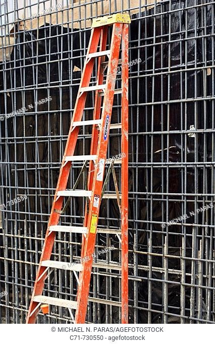 Construction step ladder leaning against a steel rebar wall