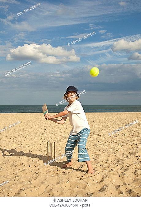 Boy playing cricket on beach