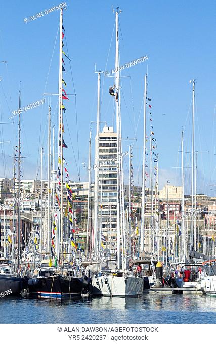 Las Palmas, Gran Canaria, Canary Islands, Spain. Sailor climbing mast as yachts prepare for the ARC (The Atlantic Rally for Cruisers) transatlantic...