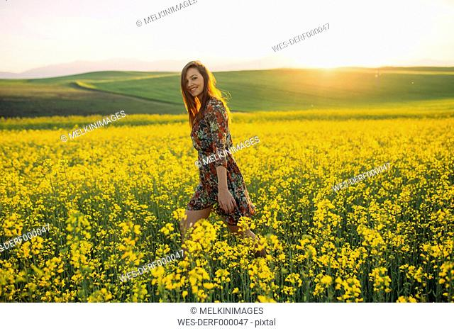 Smiling young woman walking in a rape field at twilight
