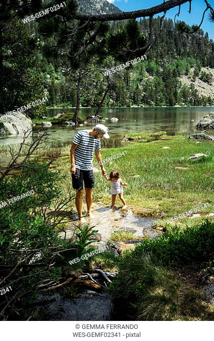 Spain, Father and daughter exploring mountain lake, standing ankle deep in water