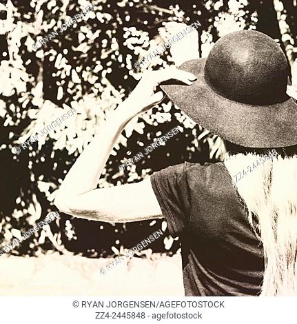 Vintage style rear view of a young female model wearing a hat in sepia toned field. Antique summer girl
