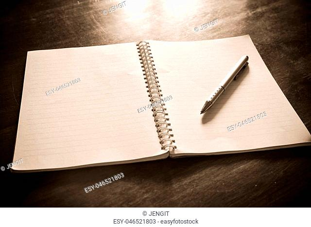 Notebook with pen on wooden table, Vintage picture tone