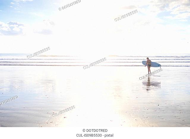 Distant view of woman carrying surfboard on beach, Nosara, Guanacaste Province, Costa Rica