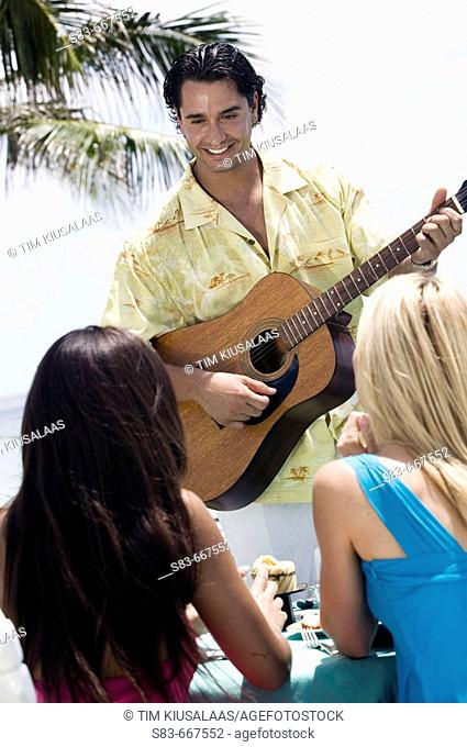 Man playing guitar for two women while they dine at the beach