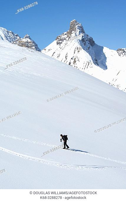 A man skis up Parker Ridge, with Hilda Peak in the background, in Banff National Park, Alberta, Canada