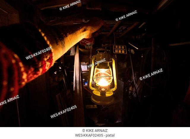 Hand holding storm lantern in a dark chamber