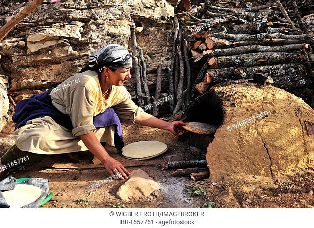 Elderly woman baking pita bread in a clay oven, Middle Atlas, Morocco, Africa