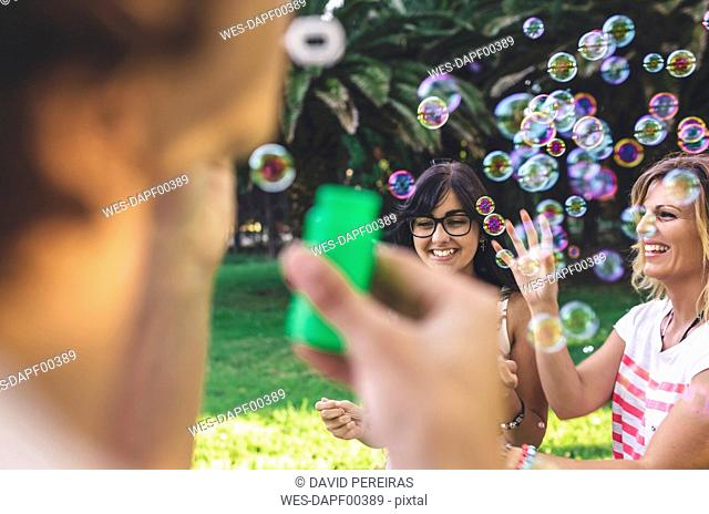 Young happy friends having fun and playing with soap bubbles in park