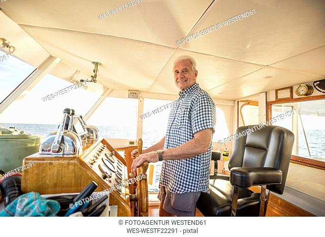 Confident senior man steering a boat