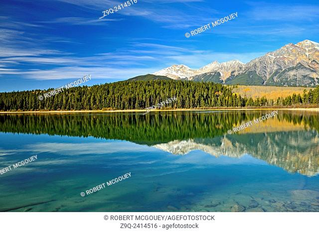 A landscape view of the calm water of Patrica Lake with Pyramid mountain reflecting in the background taken in Jasper National Park, Alberta Canada