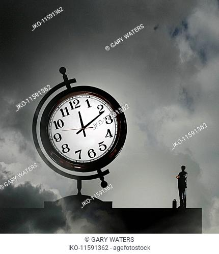 Businessman checking the time next to clock face on globe