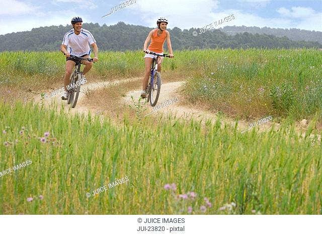 Couple riding bicycle on rural path