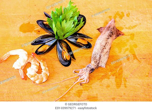 Detail of Sea food - shrimp, mussel, ink-well with green decoration on chopping board