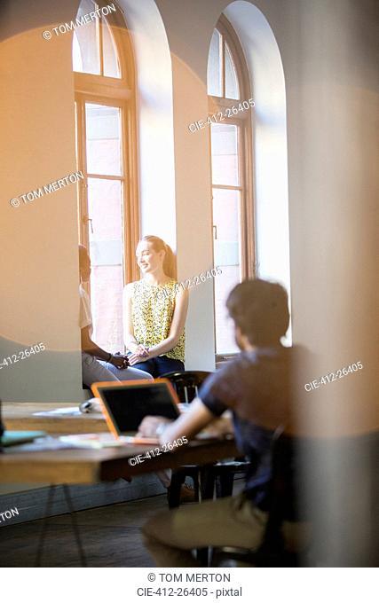 Lens flare over smiling businesswomen talking in office window
