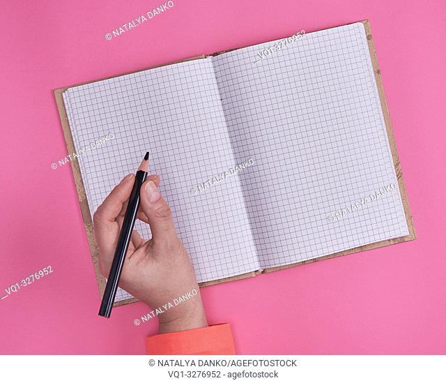 open notebook in a cell and a female hand holding a black wooden pencil, pink background, top view