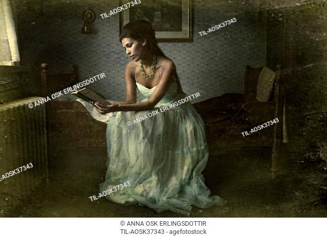 Lone female figure wearing party dress sitting on bed in small room reading a book
