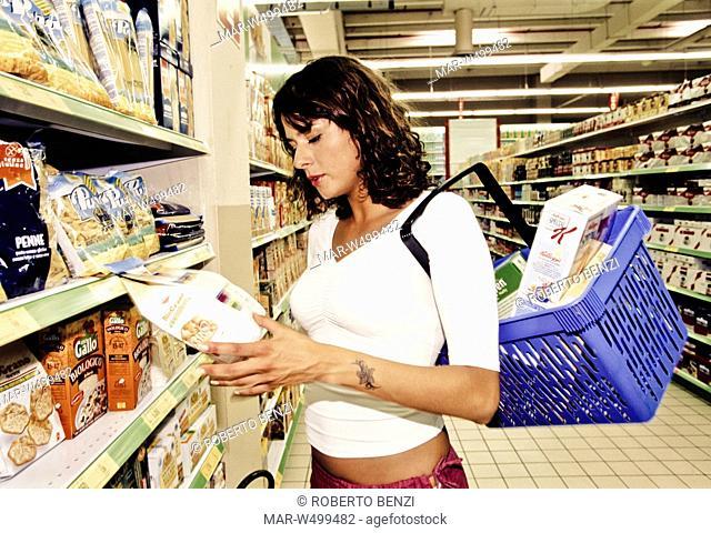 una donna al supermercato controlla l'etichetta di un prodotto
