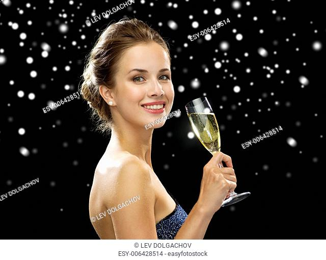 drinks, winter holidays, christmas and people concept - smiling woman in evening dress with glass of sparkling wine over black snowy background