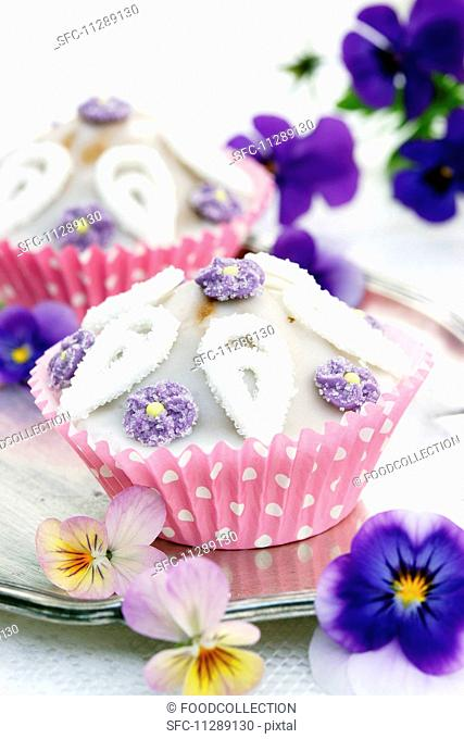 Cupcakes with sugar flowers and tufted pansies on a silver tray