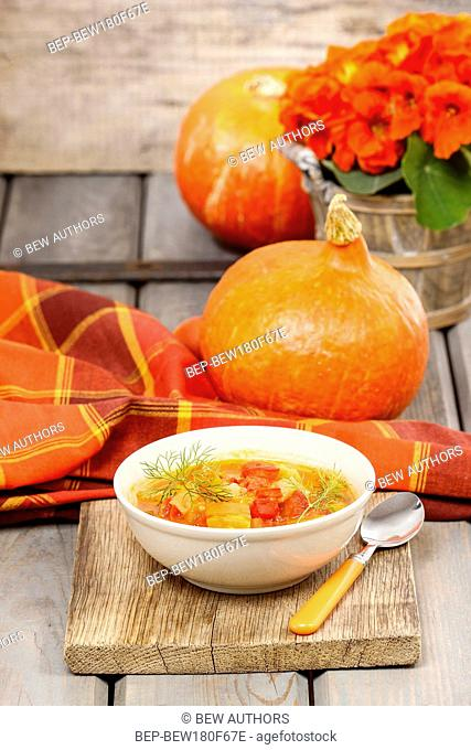 Bowl of tomato and pepper soup on wooden table. Autumn setting