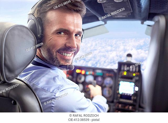 Portrait smiling, confident male pilot flying airplane in cockpit