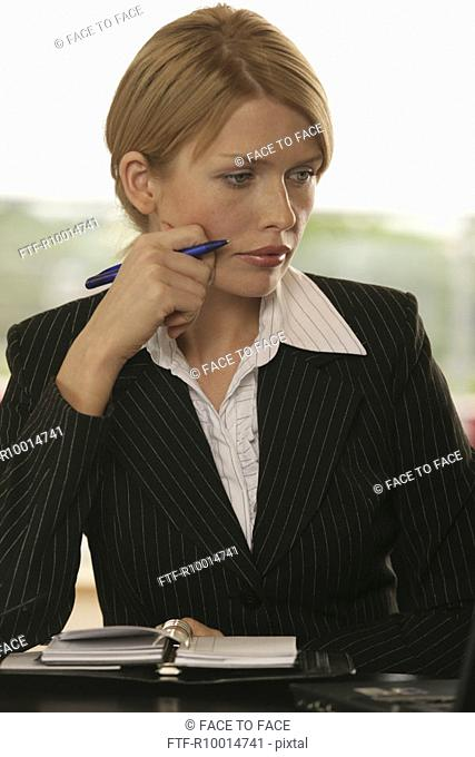 A blonde businesswoman looks at her laptop with her appointment diary beside her