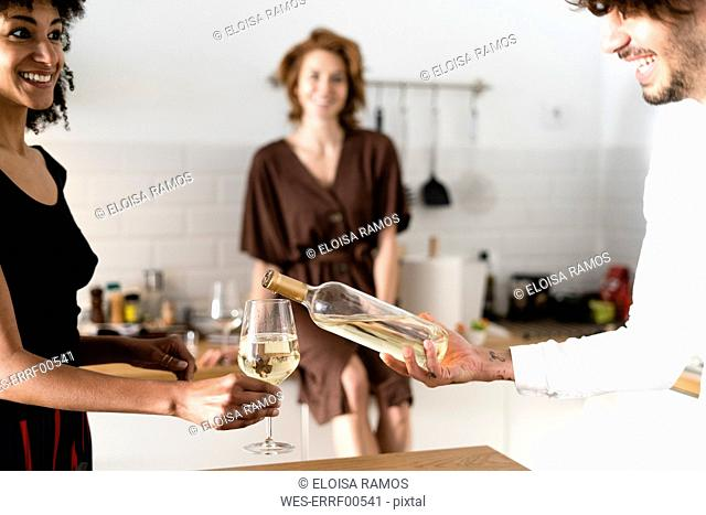 Friends standing in kitchen, drinking white wine