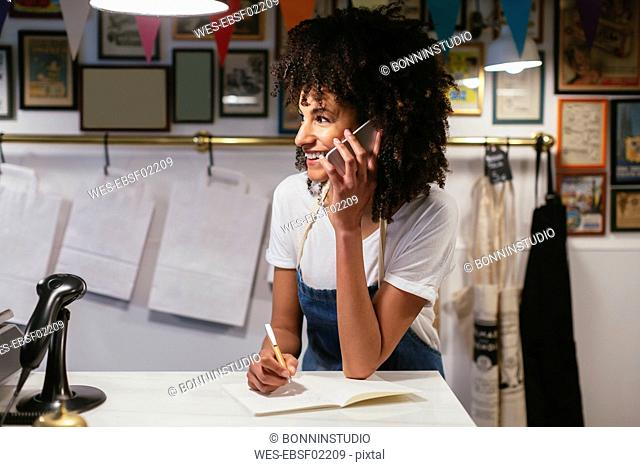 Smiling woman on the phone in a store taking notes
