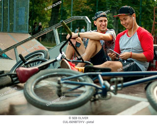 BMX cyclists resting beside ramp