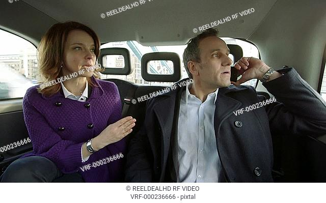 Business man and woman travel through the city in a taxi. Business man talks avidly on the phone to a colleague