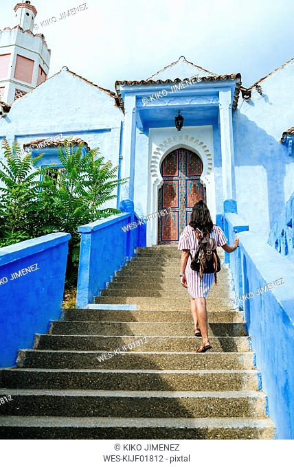 Morocco, Chefchaouen, back view of woman with backpack walking upstairs