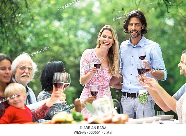 Couple holding glasses of red wine on a garden party