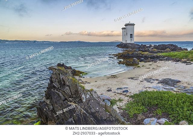 Port Ellen Lighthouse, Carraig Fhada Lighthouse in evening light after sunset with nice colors on the skye with cliffs and a small sandy beach in foreground