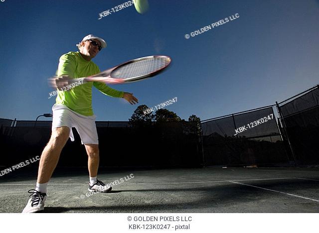 Tennis player hitting a backhand