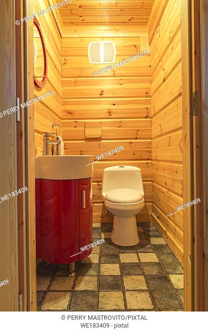 White flush toilet and lacquered wood wash sink vanity in guest washroom with ceramic tile floor inside a piece sur piece Scots pine log home, Quebec, Canada