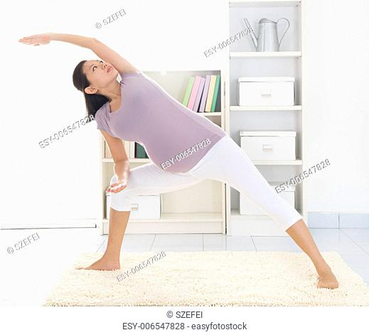 Prenatal health concept. Full length healthy 8 months pregnant calm Asian woman meditating or doing yoga exercise at home