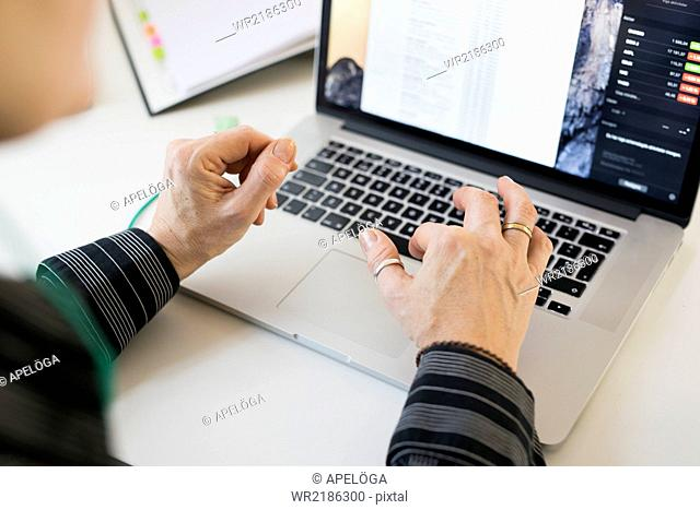 Cropped image of businesswoman's hands using laptop at desk in office
