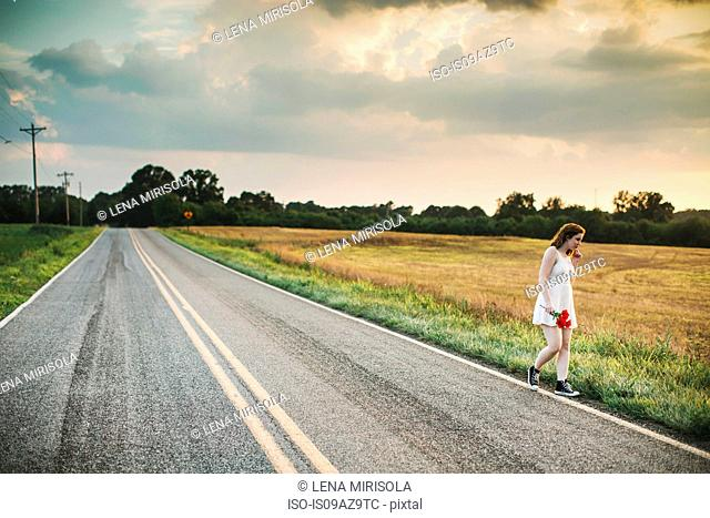 Woman holding red flowers on rural road
