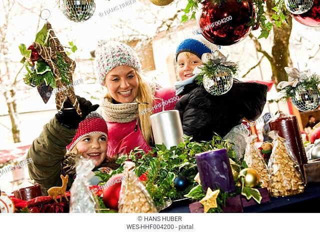 Austria, Salzburg, Mother with children at christmas market, smiling