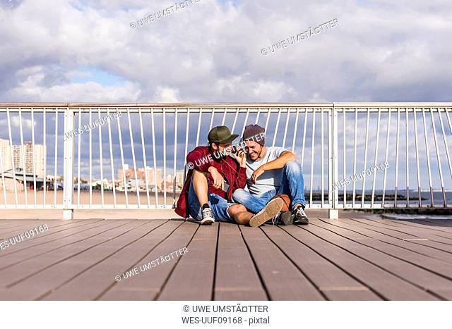 USA, New York City, two friends sitting on bridge on Coney Island sharing headphones
