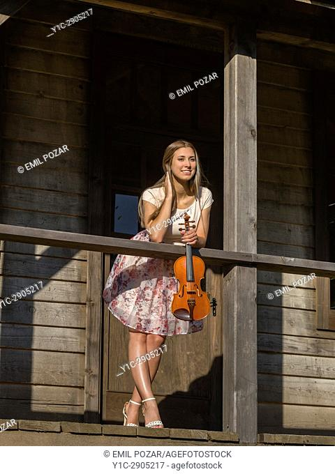 Teenager violinist outdoors inclined on wooden fence porch holding violin in wild west environment. Croatia