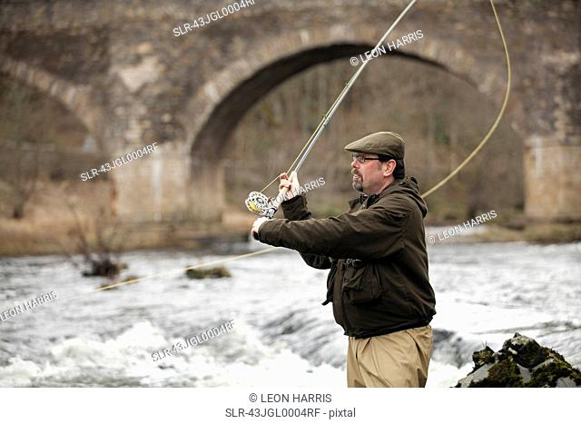 Man fishing for salmon in river