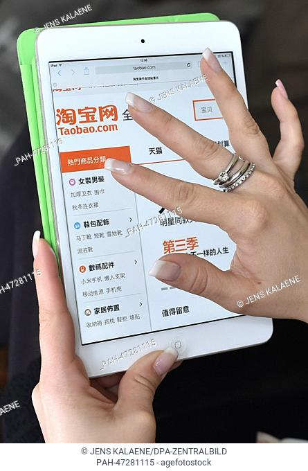 ILLUSTRATION - A young woman browses on her tablet computer through the web page of Chinese online auction platform Taobao in Berlin, Germany, 19 March 2014