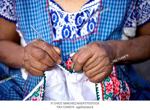 A woman stitches a design on the top of a blouse in Cuetzalan del Progreso, Mexico. Cuetzalan is a small picturesque market town nestled in the hills of...
