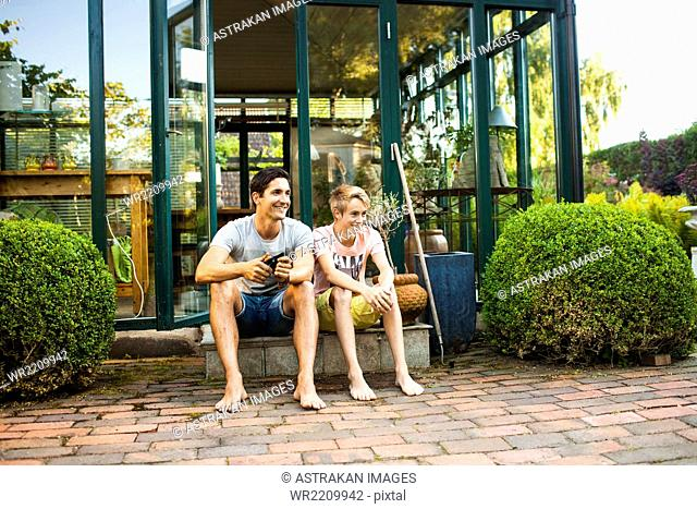 Full length of happy father and son sitting outside house