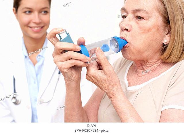 Senior woman using an inhaler, nurse watching