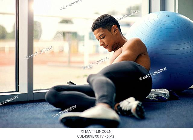 Athlete texting while resting beside exercise ball