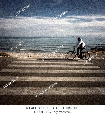 Cyclist passing pedestrian crossing on the beach, Canet, Valencia