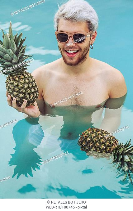 Smiling young man holding pineapples in swiming pool